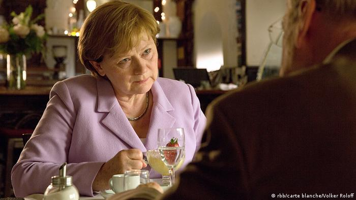 Film still from 'Die Getriebenen': a woman sits at a table, dessert in front of her, and looks at the man sitting opposite