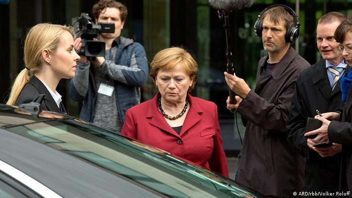 Film still Die Getriebenen A woman standing next to a car, surrounded by one other woman and two reporters with camera equipment