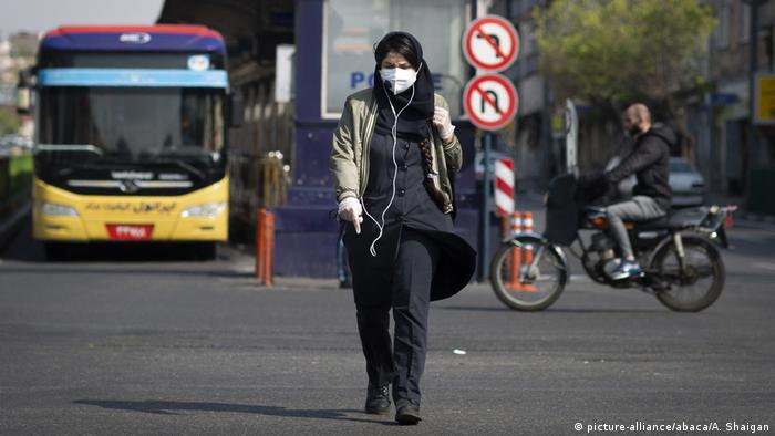A woman walking on the street in Iran wearing a face mask