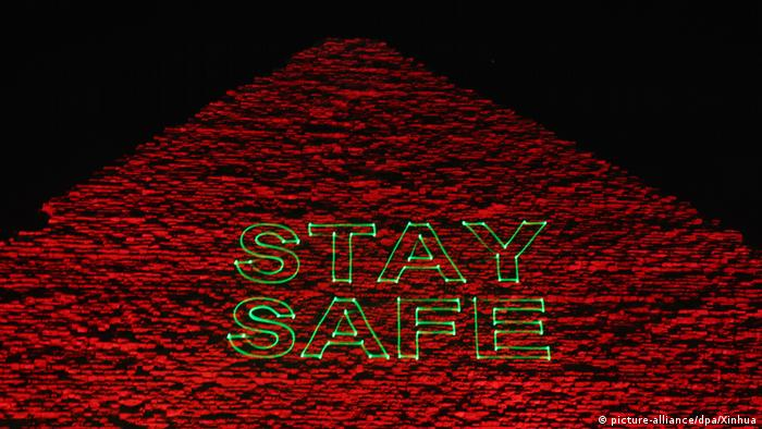 The Great Pyramid of Giza is illuminated in red light and the words Stay safe