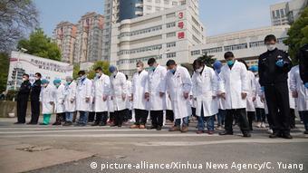 Китайские медики перед зданием клиники в Ухане склонили головы в память о жертвах коронавируса