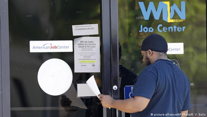 A jobless person is handed an unemployment benefit application form by a security guard behind the glass doors of a job center in Jackson, Mississippie