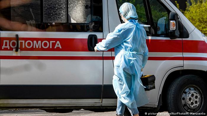 Врач в защитной одежде и медицинский микроавтобус в Киеве