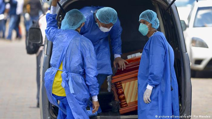 Ecuador Guayaquil people in PPE load a coffin into a car (picture-alliance/dpa/M. Pin Mendez)