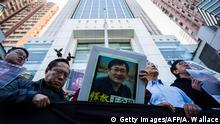eteran pro-democracy lawmaker Albert Ho (2nd L) reacts as fellow activists hold placards of detained Chinese human rights lawyer Wang Quanzhang (Getty Images/AFP/A. Wallace)