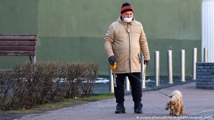 Пожилой мужчина в защитной маске выгуливает собаку