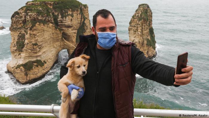 Чоловік в масці й рукавичках фотографується з собакою в Лівані
