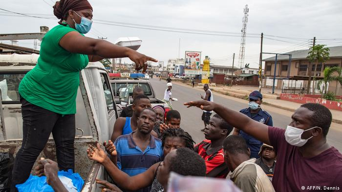 A woman on a truck distributes food among members of the public