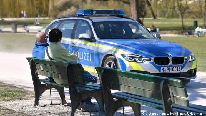 Two people sitting on bench with police car driving past (picture-alliance/SvenSimon/F. Hoermann)