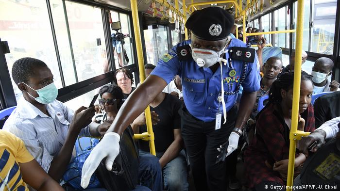 A Nigerian police officer gestures to a person on a bus
