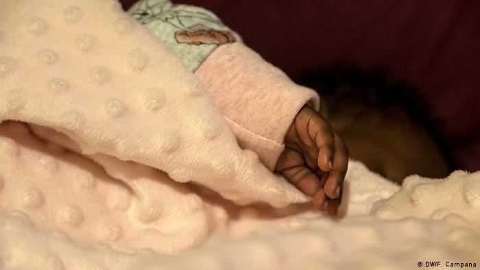 The two-month-old baby of an asylum-seeker sleeps under a blanket on the sofa at a shelter for unaccompanied minors run by the HOME Project in Athens