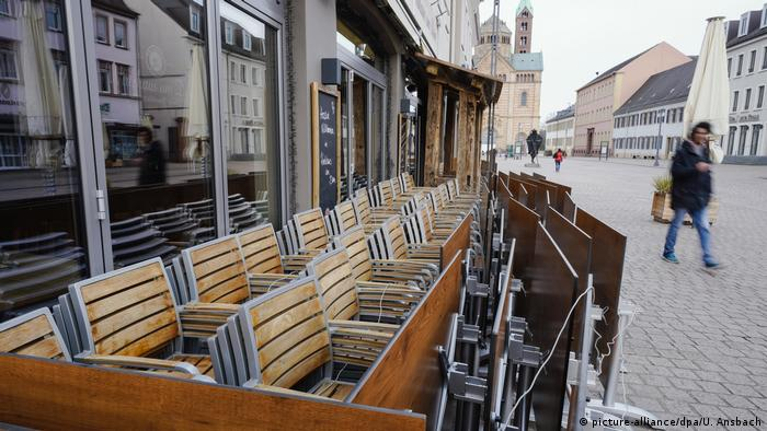 Outdoor furniture piled up close to a boarded-up and closed restaurant on the high street in Speyer, Germany. Pictured on March 26, 2020. (picture-alliance/dpa/U. Ansbach)