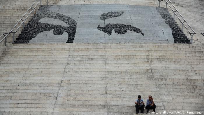 Foto de dos personas sentadas en un graderío pintado con la imagen de los ojos de Hugo Chávez