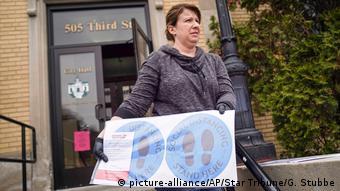Foto de una mujer con rótulos de distancia social para elecciones