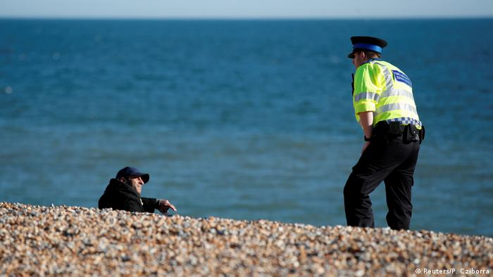 A police officer and a person on a beach in Brighton, England (Reuters/P. Cziborra)