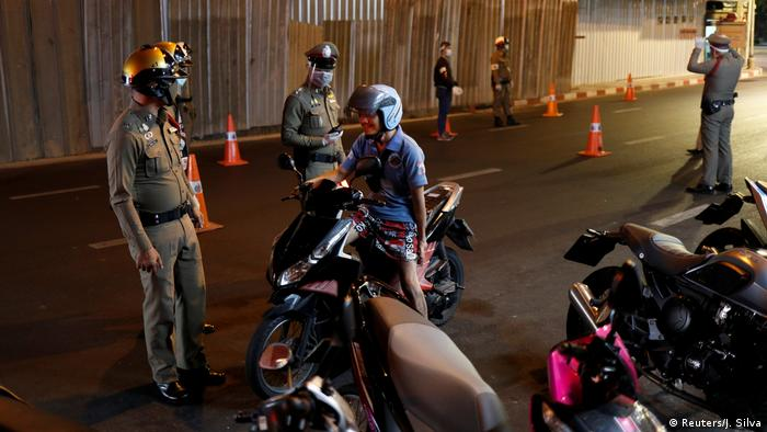 Thai police officers wearing protective masks stop a motorcycle driver (Reuters/J. Silva)