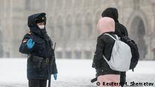 A police officer gives instructions to pedestrians, after the city authorities announced a partial lockdown ordering residents to stay at home to prevent the spread of coronavirus disease (COVID-19), during snowfall in Red Square in central Moscow, Russia March 31, 2020. REUTERS/Maxim Shemetov