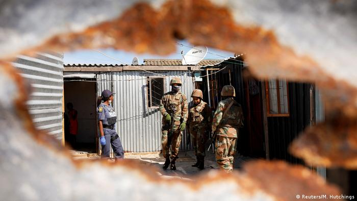 Soldiers and a police officer amid a cluster of corrrugated iron shacks