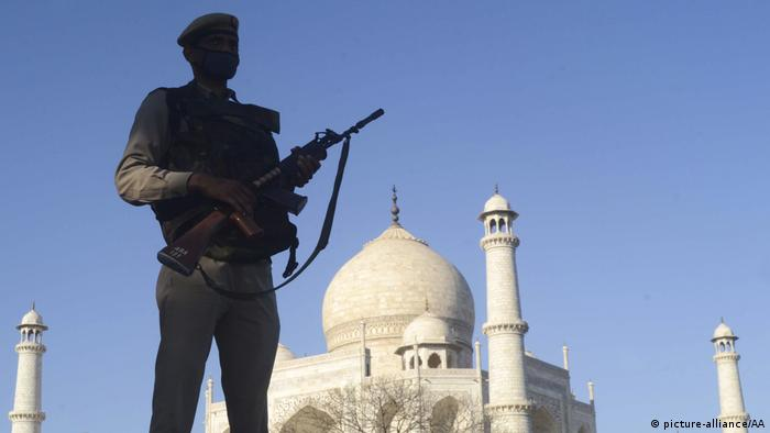 A soldier in a medical face mask stands guard outside India's historic Taj Mahal