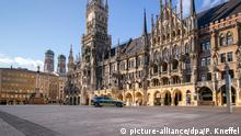 A police car drives over the almost empty Marienplatz square in Munich.- Lonely Places (picture-alliance/dpa/P. Kneffel)