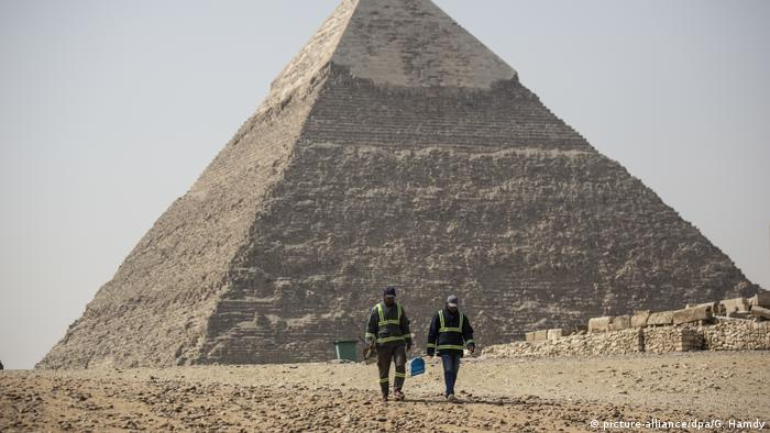 Workers with protective gear in front of the Great Pyramids in Giza, Egypt - Lonely Places (picture-alliance/dpa/G. Hamdy)