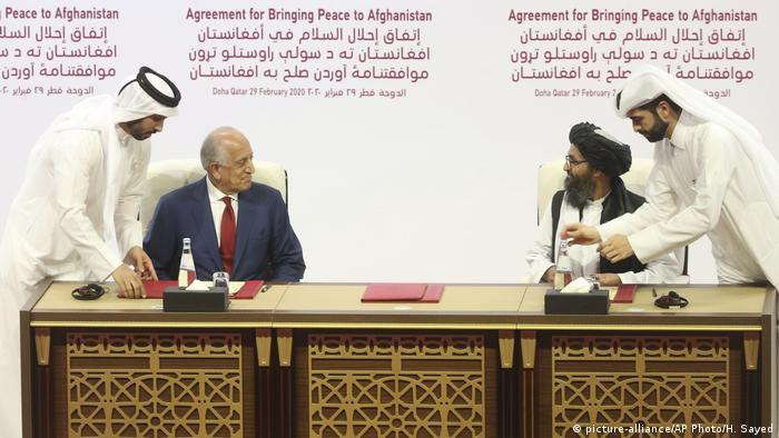 U.S. peace envoy Zalmay Khalilzad, left, and Mullah Abdul Ghani Baradar, the Taliban group's top political leader sign a peace agreement between Taliban and U.S. officials in Doha, Qatar
