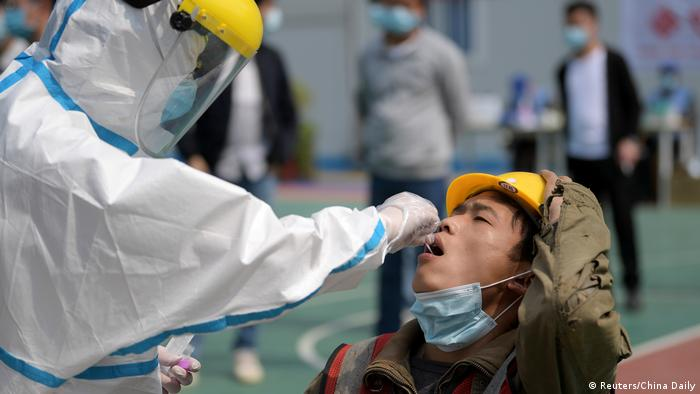 A man in a protective suit is taking a sample with a cotton swab from a man, holding his mouth open.