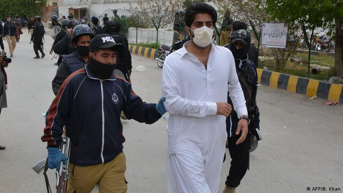 Policemen arrest a doctors in the course of a protest during a government-imposed nationwide lockdown as a preventive measure against the COVID-19 coronavirus, in Quetta on April 6, 2020