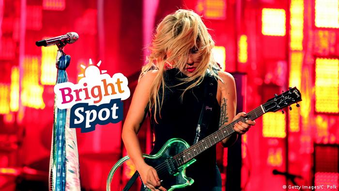 Lady Gaga plays the guitar against a bright red background