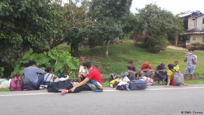 Grupo de venezuelanos na Colômbia descansa na beira da estrada, durante caminho de volta à Venezuela
