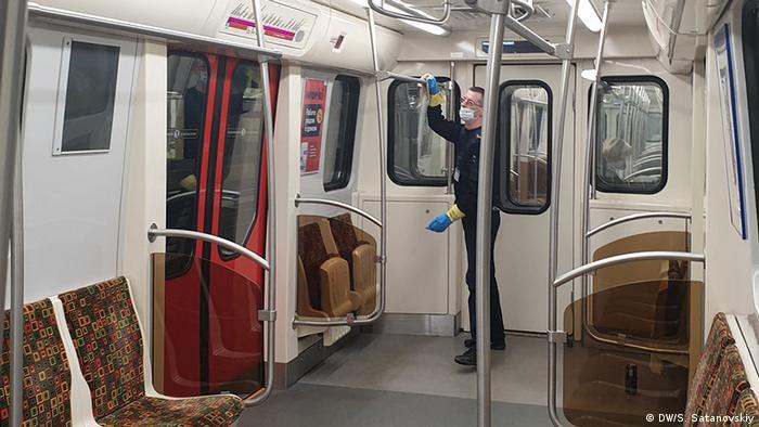 Сотрудник метро в Санкт-Петербурге протирает поручни вагонов дезинфицирующим раствором, чтобы сократить риск заражения коронавирусом.