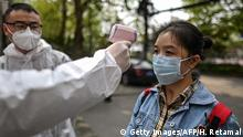 07.04.2020 *** A man wearing a protective suit checks a woman's temperature next to a residential area in Wuhan, in China's central Hubei province on April 7, 2020. - Wuhan, the central Chinese city where the coronavirus first emerged last year, partly reopened on March 28 after more than two months of near total isolation for its population of 11 million. (Photo by Hector RETAMAL / AFP) (Photo by HECTOR RETAMAL/AFP via Getty Images)
