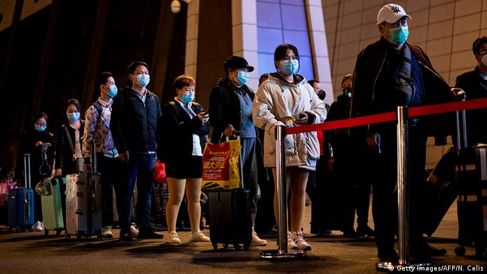 Passengers wear facemasks as they form a queue at the Wuhan Wuchang Railway Station in Wuhan, early on April 8, 2020, as they prepare to leave the city in China's central Hubei province.