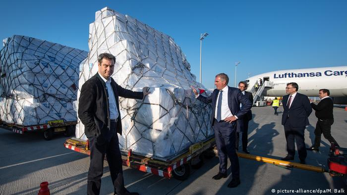 Bavarian state premier Markus Söder and Lufthansa CEO Carsten Spohr pose next to a shipment of face masks, flown in on a Lufthansa cargo plan from China. April 7, 2020.