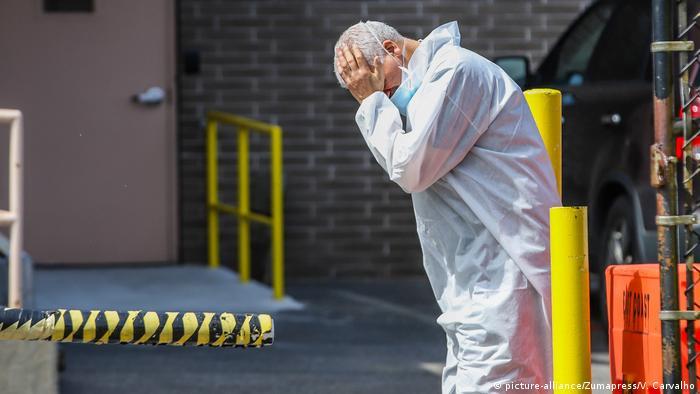 Un profesional de la salud llora delante de un hospital de la ciudad de Nueva York
