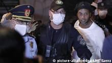 07.04.2020, Paraguay, Asuncion: Der ehemalige brasilianische Fußballstar Ronaldinho (r) kommt in einem Hotel an. Überraschend ist Ronaldinho aus der Haft in Paraguay in den Hausarrest entlassen worden. Foto: Jorge Saenz/AP/dpa +++ dpa-Bildfunk +++  