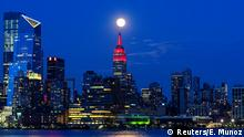 The Supermoon rises behind the Empire State Building while it glows red in solidarity with those infected with coronavirus as the outbreak of the disease (COVID-19) continues in the Manhattan borough of New York City, as it is seen from Hoboken, New Jersey, U.S., April 7, 2020. REUTERS/Eduardo Munoz