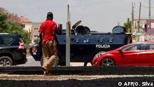A pedestrian is seen crossing a street as an armoured personnel carrier is parked in Barrio do Camama, Luanda, on April 6, 2020 to enforce a lockdown order that has largely gone unnoticed in the daily grind and hustle on the capital's streets. - Last Friday, Interior Minister Eugenio Laborinho reported that 1,209 people were detained: more than 1,000 for entering the country despite border closures, and 189 for violating the state of emergency. (Photo by Osvaldo Silva / AFP)