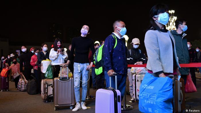 Пассажиры с чемоданами на железнодорожном вокзале в Ухане