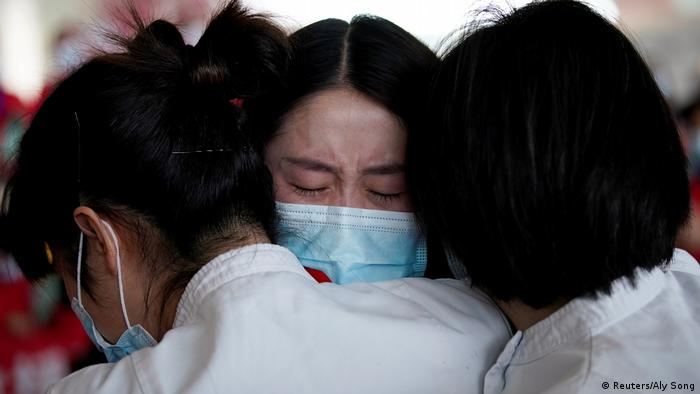 Медсестры в масках с флагами КНР обнимаются и плачут