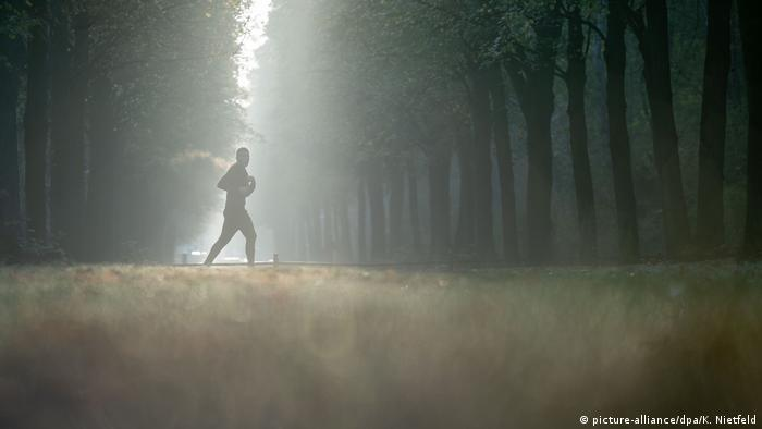 Someone jogging through the fog of a Berlin park