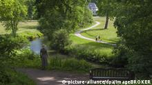 A woman in a summer dress walking along a stream in a park (picture-alliance/dpa/imageBROKER)