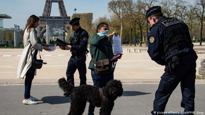 Em meio à quarentena na França, policiais controlam passantes perto da Torre Eiffel, em Paris