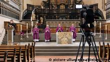 Priests holding mass in an empty church
