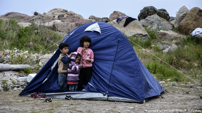 Kids stand in a tent on the island of Lesbos
