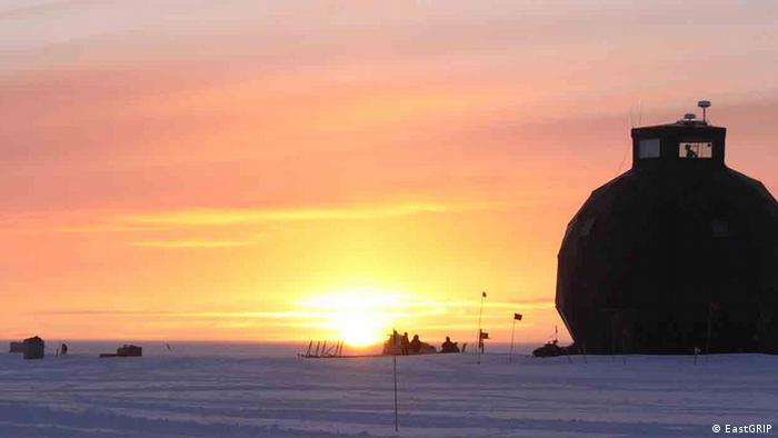 The EastGRIP research center in Greenland with the sun rising behind it