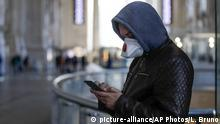 A young man in Milan, wearing a facemask, uses his smartphone. Archive photo from February 24, 2020. (picture-alliance/AP Photos/L. Bruno)