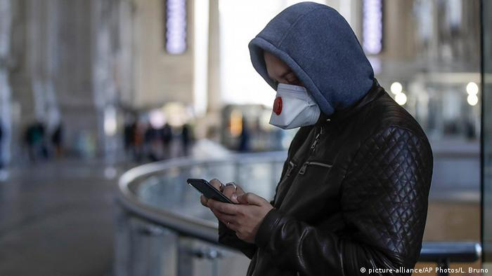 A young man in Milan, wearing a facemask, uses his smartphone. Archive photo from February 24, 2020.