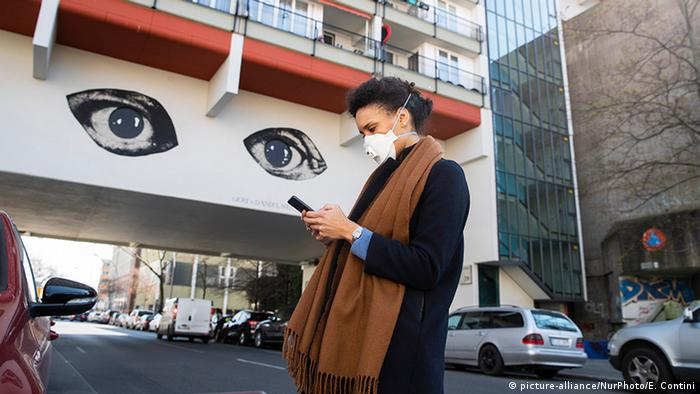 A young woman wearing a protective mask looks at her smartphone while passing by a grafitti representing two big watching eyes in Berlin, Germany on April 1, 2020.