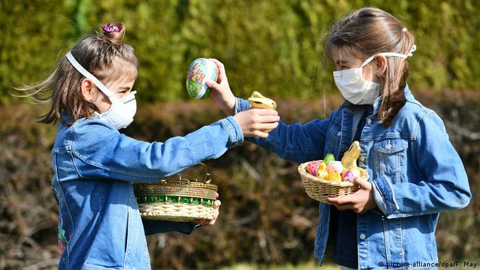 Dos niñas llevan mascarillas mientras buscan huevos de Pascua en el jardín, una tradición típica alemana. Osterode, Baja Sajonia, Alemania (27.03.2020)